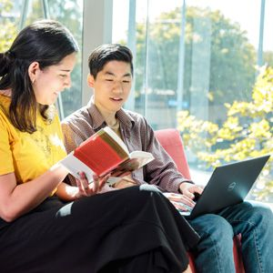 Two students accessing book and online materials while studying