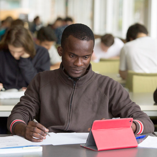 Student accessing online materials on his iPad while studying